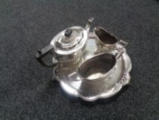 A three piece plated tea service on shaped plated tray.