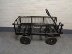 A wire metal four wheel garden trolley