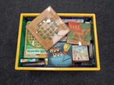 A plastic crate containing quantity of vintage and later games and puzzles