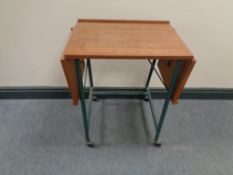 A mid 20th century teak topped bed table on tubular metal legs.