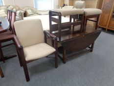 A 20th century stained beech framed armchair together with two foot stools upholstered in a beige