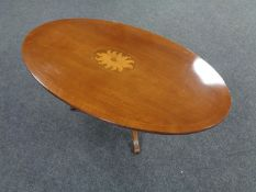 An inlaid oval pedestal coffee table.