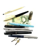 A group of fountain and ballpoint pens, £1 note, inert bullet, pocket watch keys.