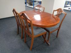 An inlaid yew wood twin pedestal dining table together with a set of four shield back chairs