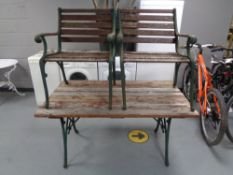 A cast iron wooden slatted garden bench with matching pair of armchairs