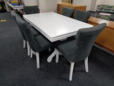 A contemporary white extending dining table on pedestal and six chairs in grey fabric