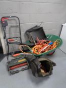 A wheelbarrow containing electric hedge trimmer, extension leads, one 10V extension lead,