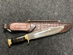 A heavy quality bowie knife with brass mounted grip and stitched leather sheath with sharpener