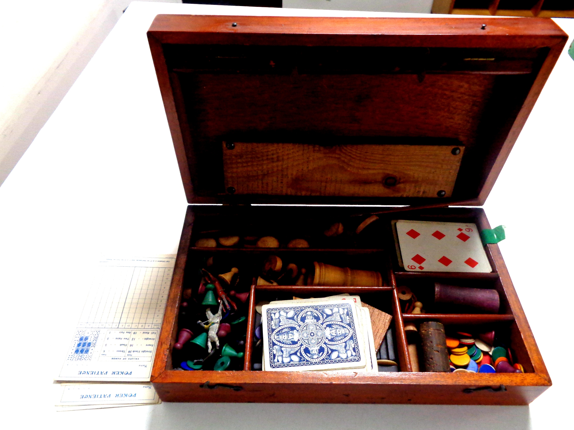 An Edwardian mahogany games box containing drafts, counters, cards,