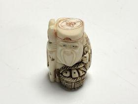 A carved Chinese bone netsuke - Gentleman holding a basket