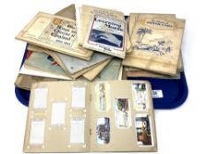 A tray of a large quantity of cigarette cards in albums, aircraft, railways,