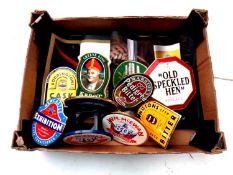 A box of a quantity of beer pump badges and drip mats
