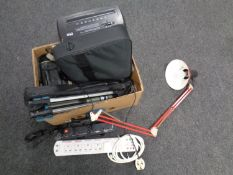 A box containing extension leads, camera tripods, angle poise lamp, laptop bag,