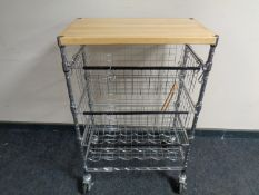 A pine topped metal three tier kitchen trolley with baskets