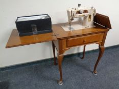 A mid 20th century Singer electric sewing machine in walnut Queen Anne table with accessories