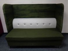 A contemporary high backed booth settee upholstered in a green and grey fabric