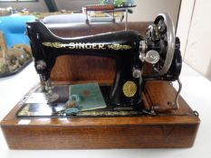 An early 20th century oak cased Singer hand sewing machine