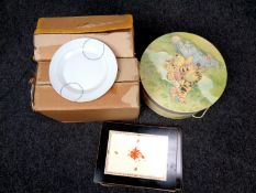 Two boxes containing ceramic dinner services together with a set of place mats and a Whinnie the