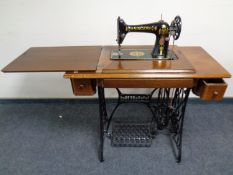 A 20th century Singer treadle sewing machine in oak table