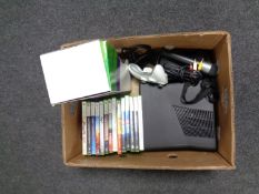 A box containing an X Box 360 with accessories and games