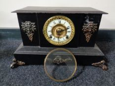 A 19th century cast iron mantel clock with brass and enamelled dial and metal mounts
