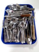 A tray containing a quantity of stainless steel cutlery