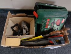 A box of vintage flat iron, hand saws,