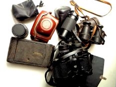 A box of assorted binoculars and cameras to include Carl Zeiss