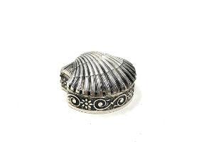 A small silver shell shaped pill box