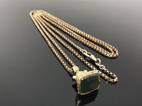 An old gold plated fob on long guard chain