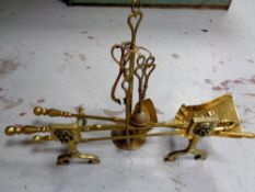 A pair of antique brass fire dogs together with three companion pieces,
