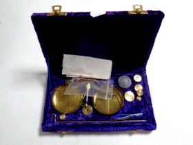 A set of miniature brass balance scales with weights in a fitted purple velvet box