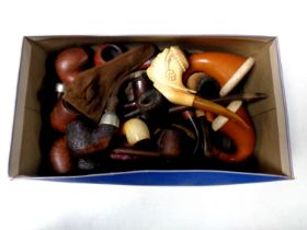 A box containing a collection of vintage pipes