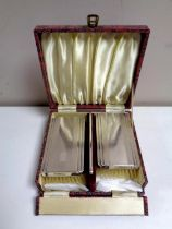 A cased three piece Birmingham silver-backed brush and comb set