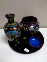 A papier mache tray containing three pieces of cloisonne