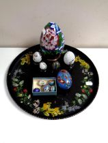 A circular papier mache tray together with eleven cloisonne eggs,