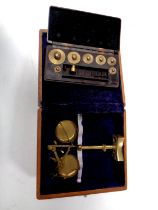 A miniature set of brass balance scales in a fitted box together with a set of miniature weights in