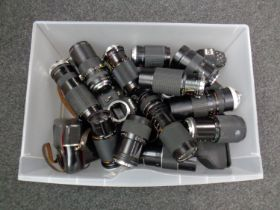 A plastic tub containing various cameras and lenses including Nikon,