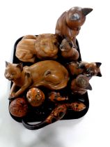 A tray containing a quantity of carved wooden cat ornaments,