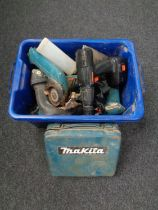 A plastic crate containing various power tools including Makita drill,