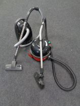 A Henry Numatic vacuum cleaner together with a Miele vacuum cleaner