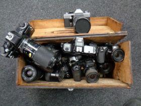 A wooden storage box containing various cameras and lenses including Praktica, Canon,