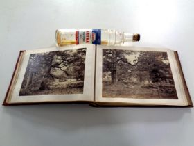 A tooled leather album containing monochrome photographs, rural scenes,