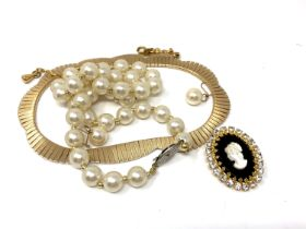 A flat link gold plated necklace together with costume pearls,