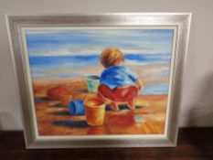 A contemporary silvered framed oil on canvas depicting a boy playing on a beach