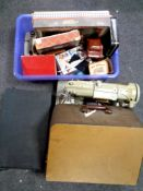 A box containing vintage puzzles and games, vintage tins, together with a suitcase, oil on board,