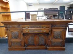 An Arts and Crafts heavily carved oak break front sideboard fitted drawers and cupboards beneath