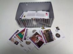 A box containing approximately 30 Royal Commemorative Coin First Day covers