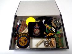 A box containing a large quantity of assorted militaria including badges and insignia, buttons,