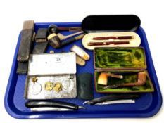 A tray containing two cut throat razors, pipes, cased pen set, cheroot, pocket knives,